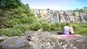 Bakflickan kramar grabben på stenen mot vattenfallet lager videofilmer
