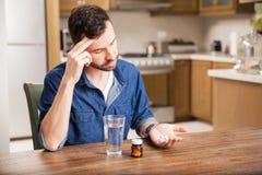 Bakfull grabb som tar några preventivpillerar Arkivfoton