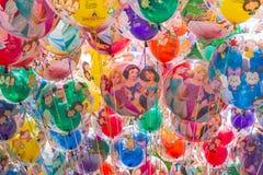 Bakgrund av ballonger med tecknad filmtecken Shanghai Disneyland är en berömd turist och en populär familjferiedestination in arkivfoton