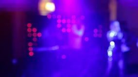 Bakgrund av dansen är det suddiga folket som dansar i en nattklubb Blått- och lilafärger stock video