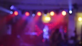 Bakgrund av dansen är det suddiga folket som dansar i en nattklubb Blått- och lilafärger arkivfilmer