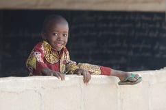 Bakgrund av den afrikanska pojken som hoppar över väggen med kopieringsutrymme Arkivbilder