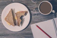 Bakgrund av den bet ostsmörgåsen på en vit rund platta, kopp av varmt kaffe, öppen anteckningsbok med en blyertspenna på den Top  arkivbilder