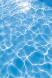 Bakgrund av den krusiga modellen av rent vatten i en blå simning Arkivfoton