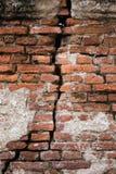 Bakgrund av den smutsiga brutna tegelstenväggen för gammal tappning med skalningsmurbruk, textur Arkivbild