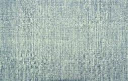 Bakgrund av det gråa klassiska ljuset - - blått texturerat tyg arkivfoto