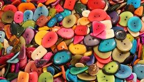 bakgrund av färgrika knappar som göras med torkat, gömma i handflatan frö Arkivfoton