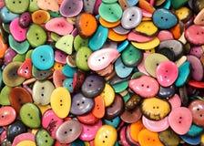 bakgrund av färgrika knappar som göras med torkat, gömma i handflatan frö för sa Fotografering för Bildbyråer