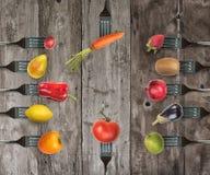 Bakgrund av gafflar med olika grönsaker och frukter Royaltyfri Fotografi