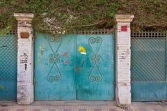 Bakgrund av gröna gamla red ut antika smidesjärnportar för grunge med blom- modellprydnader och två vita tegelstenkolonner royaltyfri foto