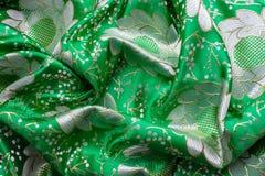 Bakgrund av grönt tyg med blommor Arkivfoton