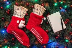 Bakgrund av granfilialer Jultomten röda strumpor med pengar klaus santa för frost för påsekortjul sky Top beskådar Xmas-lyckönska royaltyfri fotografi