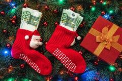 Bakgrund av granfilialer Jultomten röda strumpor med pengar och gåvan klaus santa för frost för påsekortjul sky Top beskådar Xmas royaltyfria foton