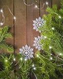 Bakgrund av granris med snöflingor och ljus på den bästa sikten för träyttersida royaltyfri bild