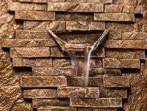 Bakgrund av guld- brunt stenar tegelstenar med vatten som faller från utloppsröret royaltyfri foto