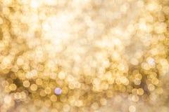 Bakgrund av guld- ljus med bokeheffekt Arkivbild