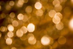 Bakgrund av guld- ljus med bokeheffekt Royaltyfria Bilder