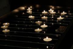 Bakgrund av många tända stearinljus i basilika Arkivfoto