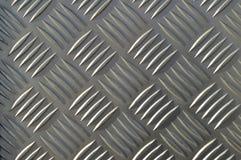 Bakgrund av metall med upprepande modelldiamanter arkivbild