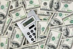 Bakgrund av räkningar för $ 100 och en räknemaskin Arkivbild