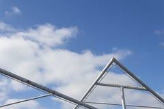 Bakgrund av rör i geometriska former mot en blå himmel med moln Royaltyfri Fotografi