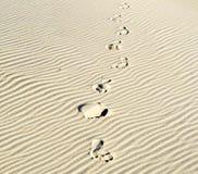 Bakgrund av sand skvalpar på stranden med tryck av fot Royaltyfri Fotografi