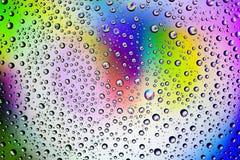 Bakgrund av små droppar på exponeringsglaset och defärgade målarfärgslaglängderna arkivfoton