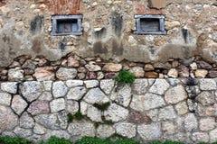 Bakgrund av stenväggen med små träfönster arkivbilder