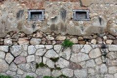Bakgrund av stenväggen med små träfönster royaltyfria bilder