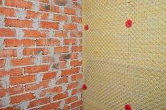 Bakgrund av tegelstenväggen och en vägg av isolering arkivfoto