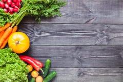 Bakgrund av träsvarta plankor med nya grönsaker Royaltyfria Foton