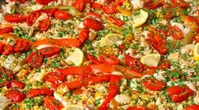 Bakgrund av Valencian paella med ris och ärtor och röd tomat Royaltyfri Fotografi
