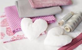 Bakgrund av vit textilhjärtor och syhjälpmedel och tillbehör i rosa - bild arkivbild