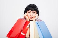 bakgrund bags brunett över vitt kvinnabarn för shopping Arkivfoto