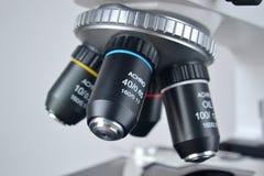 bakgrund bak det blåa closeuplutningmikroskopet royaltyfri bild