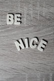 Bakgrund Bokstäver på trätabellen ` Är trevlig `, Royaltyfri Bild