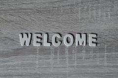 Bakgrund Bokstäver på trätabellen Välkommen ` för `, Royaltyfri Foto