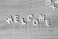 Bakgrund Bokstäver på trätabellen Välkommen ` för `, Arkivbild