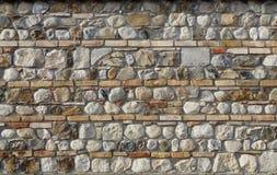 bakgrund 3d framför texturväggen Naturliga stenar som strös in med linjer av horisontaltegelstenar Royaltyfria Foton