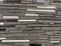 Bakgrund eller tapet av gångbanan som göras av betong som dekoreras med svart, vit, och grå färggranit- eller marmortegelplattor Arkivbilder