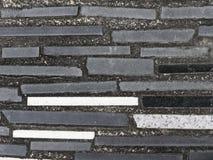 Bakgrund eller tapet av gångbanan som göras av betong som dekoreras med svart, vit, och grå färggranit- eller marmortegelplattor Arkivbild