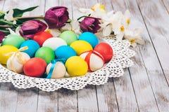 bakgrund färgade vektorn för tulpan för formatet för easter ägg eps8 den röda Kulöra easter ägg och vårblommor på vit träbakgrund Royaltyfri Bild