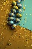 bakgrund färgrika easter Guld- konfettier på kulöra ark Bästa sikt av dekorordningar royaltyfri fotografi