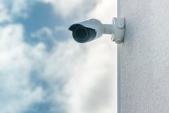 Bakgrund för blå himmel för CCTV-säkerhetskamera som främst installeras på den vita byggande väggen fotografering för bildbyråer