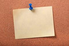 Bakgrund för bräde för kork för häftstift för stolpe för singel gul klibbig anmärkning klämd fast Arkivfoto