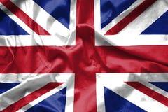 Bakgrund för brittUK-flagga som vinkar med tygtextur Royaltyfri Foto