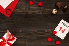 Bakgrund för dag för valentin` s med kopieringsutrymme Kort för dag för valentin` s, gåvaask och choklad på trätabellen Royaltyfri Bild