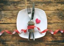 Bakgrund för dag för valentin` s, vit platta, gaffel, kniv, band, honom Arkivbilder