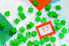 Bakgrund för dag för St Patrick ` s festlig Gröna quatrefoils och irländsk flagga som täcker kalendern med inramat 17 mars Arkivfoto