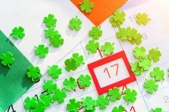 Bakgrund för dag för St Patrick ` s festlig Gröna quatrefoils och irländsk flagga som täcker kalendern med inramat 17 mars Arkivbild